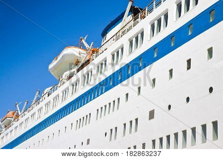 Large cruise ship with lifeboats on blue background