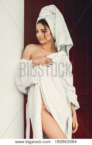 sexy young girl with dark hair, big eyes and dark eyebrows wearing white bath robe whith towel on her head. Model with light nude make-up, white studio background, beauty photo