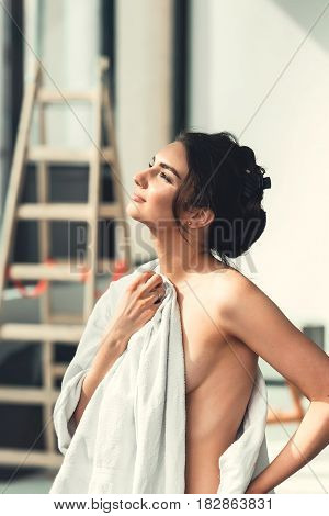 Sexy young brunette woman standing before window and admiring sunrise or sunset covering her naked body with towel after bath. Big light room