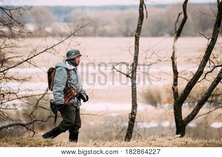 Rogachev, Belarus - February 25, 2017: Re-enactor Dressed As German Wehrmacht Infantry Soldier In WW II Walking In Autumn Forest.
