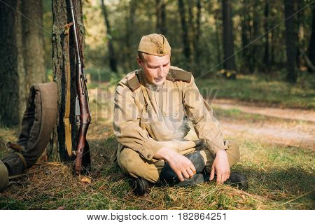 Dyatlovichi, Belarus - October 1, 2016: Tired Reenactor Man Dressed As Russian Soviet Red Army Infantry Soldier Of World War II Stopped To Rest During A Campaign In Forest