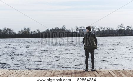 teenager standing on the edge of a pier near a river