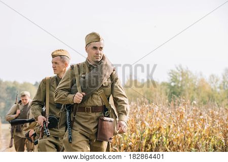 Dyatlovichi, Belarus - October 1, 2016: Reenactors Men Dressed As Russian Soviet Red Army Infantry Soldiers Of World War II Marching In Field With Weapon Machine-gun At Historical Reenactment