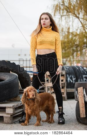 Portrait. Beautiful sexy girl, blond, young woman looking like Jennifer Aniston standing with a dog cocker spaniel, on a background of rubber wheels abandoned, wooden pallets.
