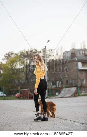 Portrait. A beautiful sexy girl, blonde, a young woman looking like Jennifer Aniston is standing with a Cocker Spaniel dog, against a backdrop of urban homes in a sleeping area.