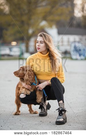 Portrait. A beautiful sexy girl, blonde, a young woman looking like Jennifer Aniston is siting with a Cocker Spaniel dog, against a backdrop of urban homes in a sleeping area.
