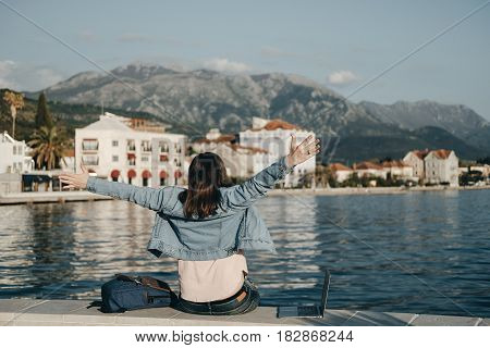 Back View Of Happy Woman Raised Hands Sitting On Embankment With Laptop. Vacations, Freelancer, Life