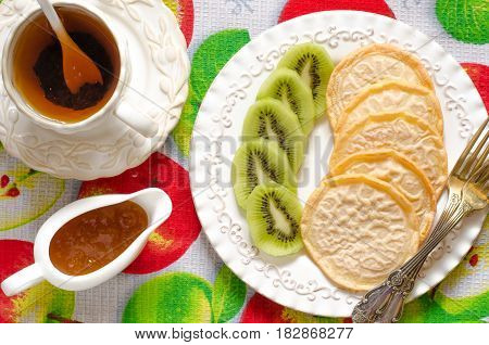Vegan pancakes with kiwi tea and jam