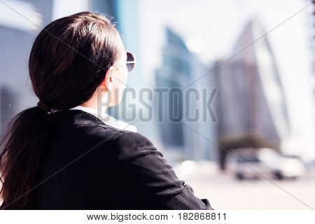 a businesswoman or architect standing in the streets of dubai and looking at a construction site