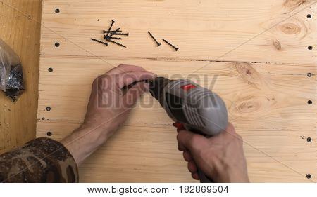 Hands of a carpenter screwing screws in wooden boards