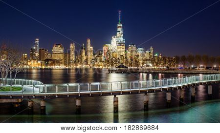 New York City Financial District skyscrapers and Hudson River from Hoboken promenade in evening. Lower Manhattan skyline and pedestrian bridge from New Jersey