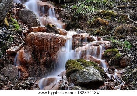 Sources with ferrous impurities flowing over large stones.
