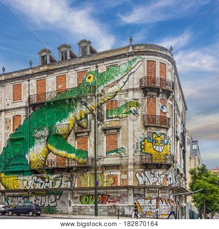Lisbon, Portugal - April 4, 2017: Lisbon street art. graffiti green crocodile. Painting house Avenida Fontes Pereira de Melo Lisboa Portugal.