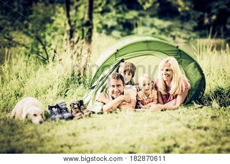 a family is camping by the lakeside