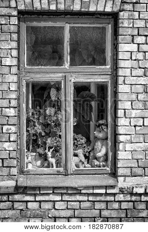 Window with wooden frames and color crumbled away. Outside the window in the old toys.