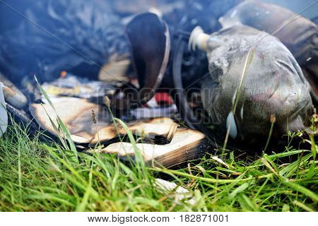 In the grass lying fire damaged things and paper.