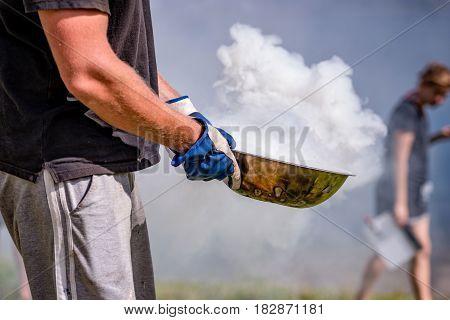 Film industry. Man brings spewing smoke dish.