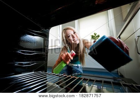young blond holding a sponge and cleaner and looking into the oven