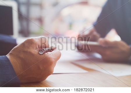 Two Young Businessmen Using Touchpad And Analysis Business Chart Document At Meeting