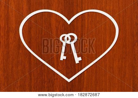 Paper heart with keys inside on wooden background. Housing family concept. Abstract conceptual image