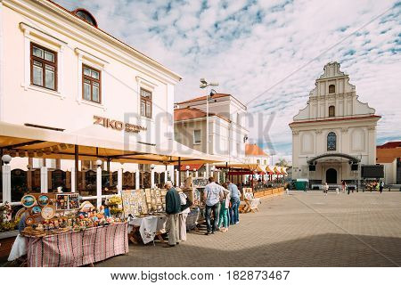 Minsk, Belarus - September 3, 2016: People Walking Near Street Market In Freedom Square Near Monastery Of The Holy Spirit Bazilianok. Trading Trays With Sale Of Gifts, Sweets And Souvenirs