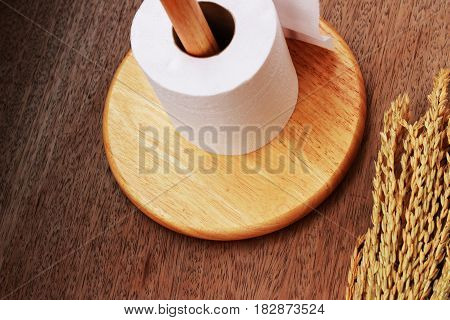 Wooden toilet paper holder placed on a brown background.