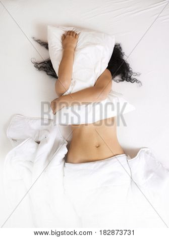 Young Woman Lying In Bed And Holding A Pillow Who Hides Her Face.