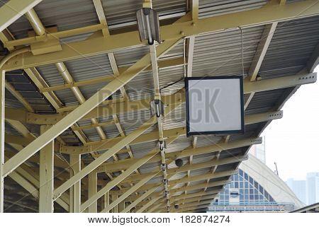 board on ceiling in train station platform