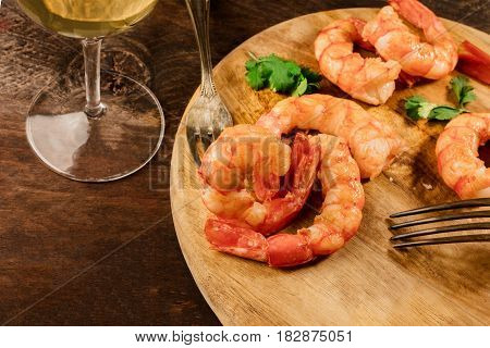 A photo of cooked shrimps with cilantro leaves, flakes of salt, a glass of white wine, and a place for text