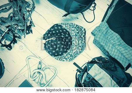 Outfit of traveler climber student teenager. Overhead of essentials for modern sport young person. Different objects on white wooden background