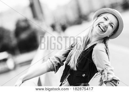 Happy hipster girl in hat on city street