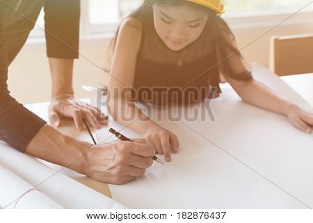 Little Engineer Girl In The Safety Helmet With A Construction Blueprint With Guidance Of Her Teacher