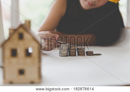 Little Asian Girl Put Coin To Money Stack - Money Saving Education Concept