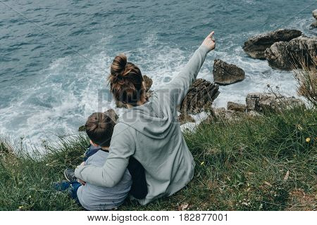 Happy Together. Mother And Her Son Raised Their Hands Upwards Sitting On The Mountain Above The Sea.