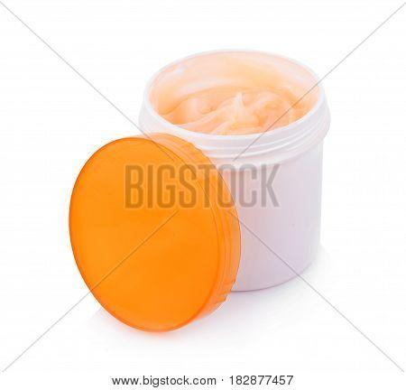 Moisturizing cream in an open jar on white background