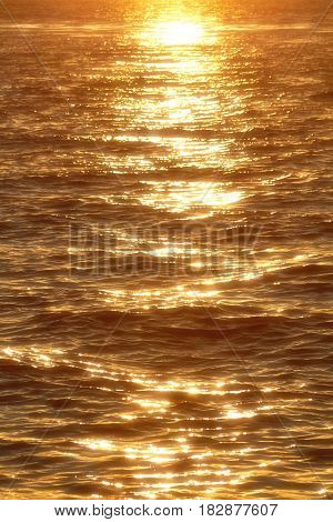 Sun rays reflected on a water surface in motion.