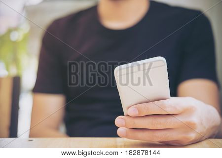 A man holding and using smart phone in modern cafe