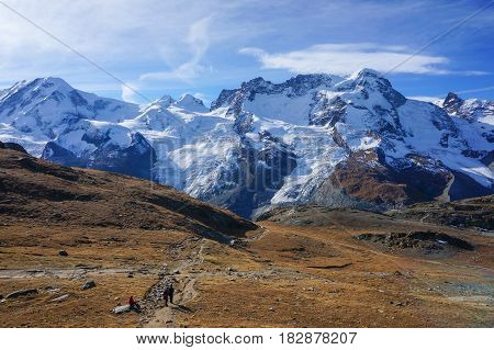 View of people hiking on red cold stone rock mountain with the background of snow alps in autumn