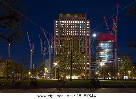 large size construction cranes at buidling construction site in London England at night with people in public park in foreground