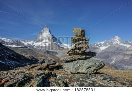 Compare concept of balance stable and equal rocks on the alp with matterhorn in background Switzerland