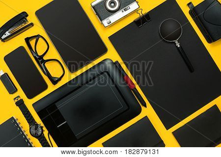 Workplace with office items and business elements on a yellow background. Concept for branding. Top view. Copy space. Still life