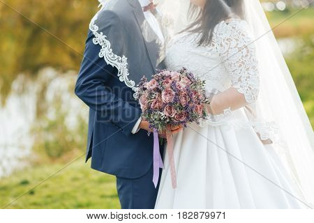 the bride and groom on your wedding day for a walk holding wedding bouquet. The groom and the bride covered by a veil