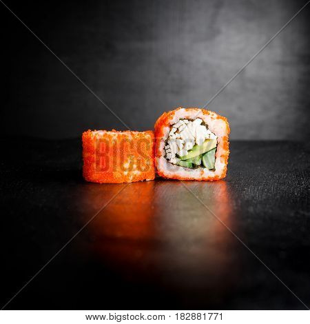 Sushi rolls on dark background. Japanese traditional food.