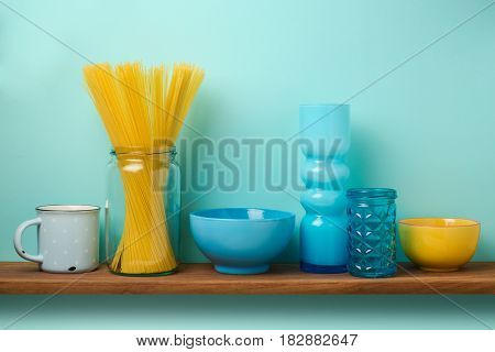 Kitchen shelf with pasta and dishes over blue background
