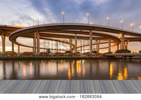 Opening wooden floor Round highway interchange with sunset sky backround and river front Bangkok Thailand transportation backrgound