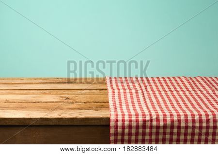 Empty wooden table covered with red checked tablecloth. Background for product montage display