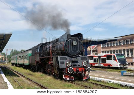Railways steam locomotive with wagons standing the station the electric train in the background