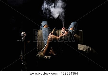 naked girl smoking hookah pretty woman with sexy back and body in jeans sitting on eastern chair with shisha bong or kalian as arabic tradition on black background