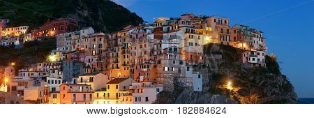 Panoramic view of Italian style resident buildings over cliff in Manarola in Cinque Terre at night, Italy.