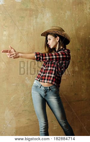Nonverbal communication gunfighter. Pretty girl or sexy woman with blond long hair in stylish cowboy hat red plaid shirt and blue jeans showing finger gun hand gesture on beige wall background